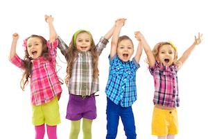 Glade små børn står hånd i hånd med armene over hovedet og leger