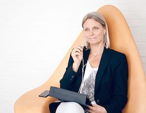 Dansk dame sidder i orange designerstol med en iPad på skødet og høretelefoner i ørene og lytter efter