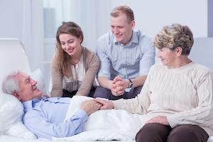 Pårørende familie til en syg mand indlagt på et sygehus, sidder og giver ham mentalt støtte i sin seng