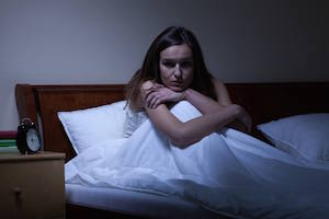 Siddende kvinde med søvnrædsel er lige vågnet af et verbalt udbrud efter et mareridt, som hun ikke husker