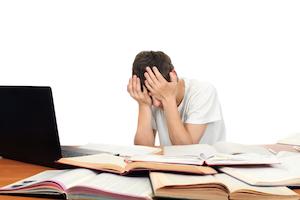 Barn med Indlæringsvanskeligheder tager sig til hovedet i frustration over ikke at kunne overskue sine lektier