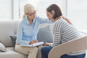 Kvindelig terapeut reagerer på sin klients grædende adfærd og trøster hende beroligende, mens hun tager noter.
