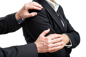 Chef med konflikthåndteringsproblemer tager medarbejder over skulderen, for at signalere at de sproglige kompetencer indenfor konflikthåndtering er begrænsede