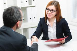 Smilende forretningskvinde giver håndtryk til jobsøgende, som indikerer en vellykket jobsamtale med en jobløs mand