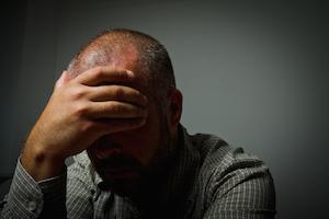 Udbrændt mand tager sig selv til hovedet, som symbol på at han ikke kan overskue de basale hverdagsopgaver længere